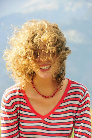 enclose: Smiling woman's hair blowing in wind