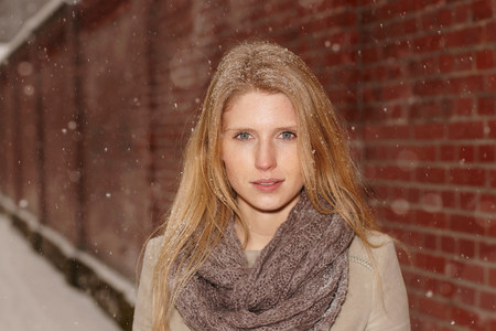 wintry weather: Woman with brick wall behind her