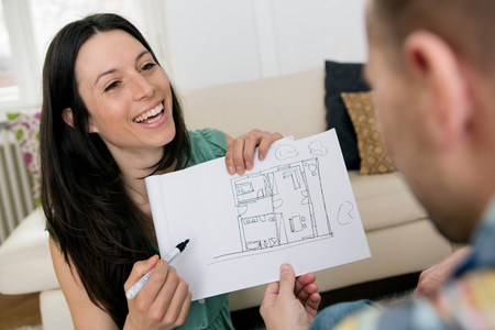 parlours: Mid adult couple sketching house plans