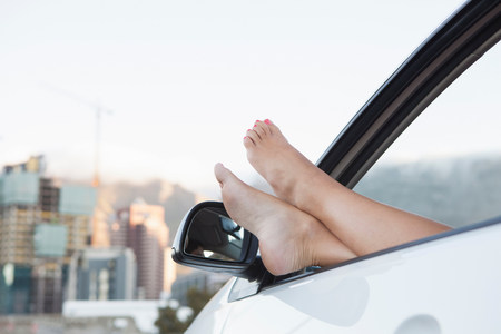 Young woman with feet up through car window