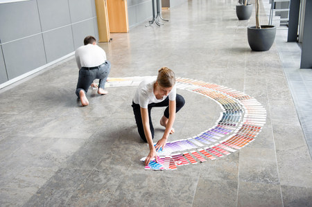 Young woman and mid adult man arranging swatches on lobby floor
