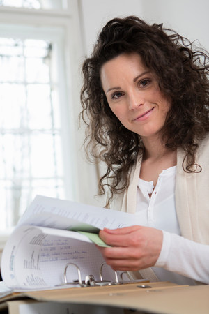 turning the page: Woman turning pages of paperwork in folder
