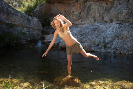 Young woman balancing on rock in stream