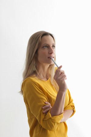 通信: Woman in yellow top biting pen LANG_EVOIMAGES