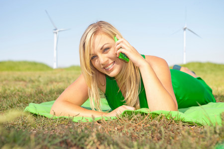 Woman lying in field on green cell phone LANG_EVOIMAGES