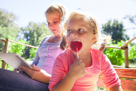 handheld device: Mother using laptop,girl with lollipop