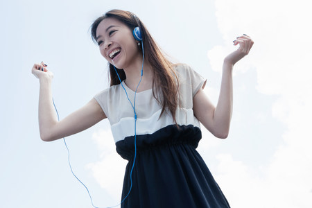 pleasurable: Young woman wearing headphones dancing LANG_EVOIMAGES