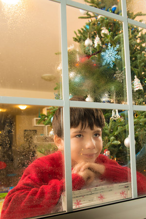 parlours: Boy staring out of window on christmas eve LANG_EVOIMAGES