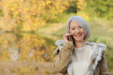 Portrait of senior woman on cellphone outdoors LANG_EVOIMAGES