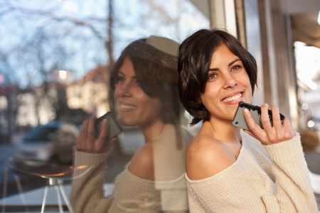pleasurable: Portrait of woman outside cafe holding cell phone LANG_EVOIMAGES