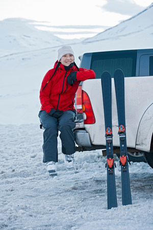 Woman sitting on back of pick up truck with skis