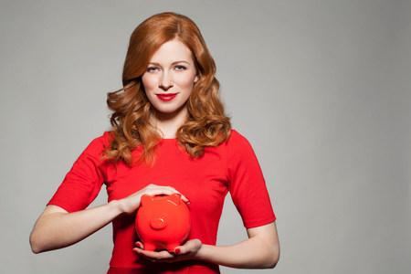 health equity: Woman holding red piggy bank