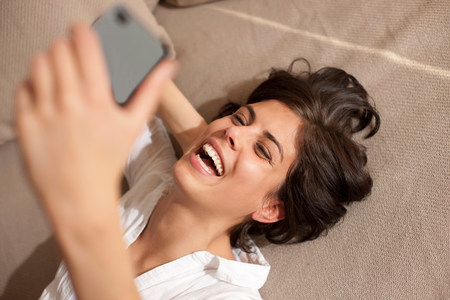 Portrait of woman lying on sofa holding cell phone LANG_EVOIMAGES