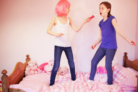 pinks: Two girls standing on bed singing into microphone