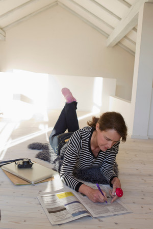 attics: Woman lying on floor with classified ads