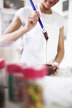 pleasurable: Woman pouring melted chocolate LANG_EVOIMAGES