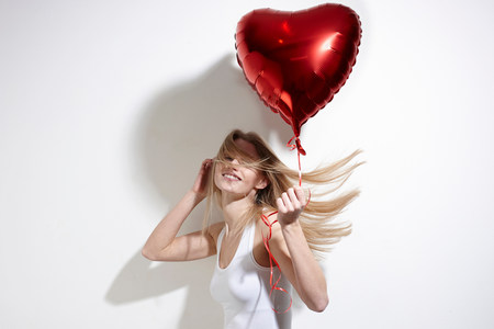 obscuring: Woman with red heart-shaped balloon LANG_EVOIMAGES