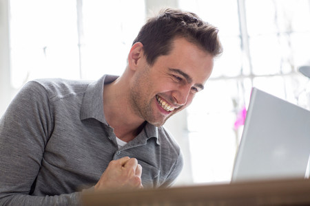 50 54 years: Mature man looking at computer and smiling