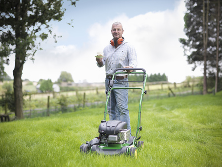 Man with lawn mower having cup of tea