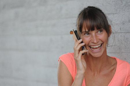 enthusiastically: Woman talking on cell phone outdoors