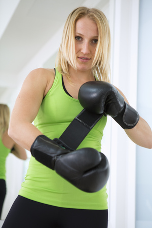 Boxer putting on boxing gloves in gym