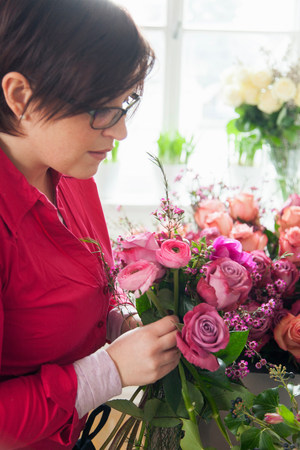 Young woman arranging fresh flowers into bouquet LANG_EVOIMAGES