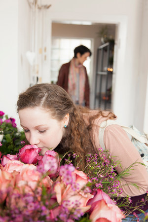 inhalation: Teenage girl smelling bouquet in florists