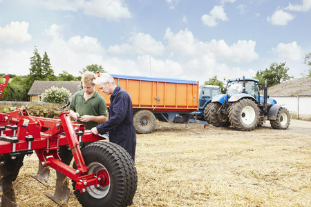 gather: Farmers adjusting machinery in field
