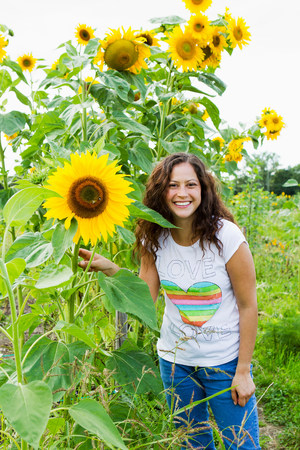 Portrait of young woman with yellow sunflowers in allotment LANG_EVOIMAGES