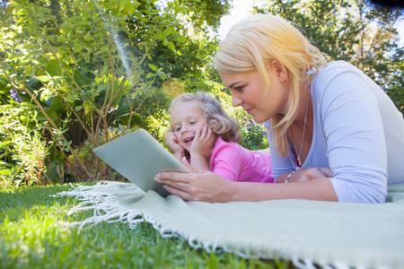 Mother and daughter lying on blanket in garden using digital tablet LANG_EVOIMAGES