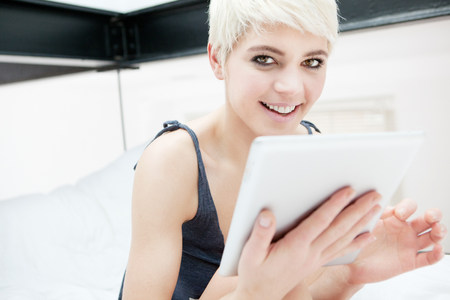 Woman lying on bed using digital tablet