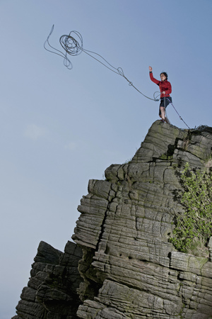 Rock climber tossing rope over cliff LANG_EVOIMAGES