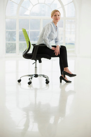 Businesswoman sitting on office chair in sparse white room LANG_EVOIMAGES