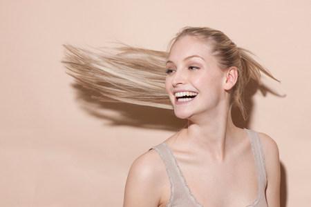 flicking: Young blonde woman flicking hair LANG_EVOIMAGES