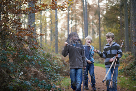 giggling: Boys walking through forest with fishing equipment