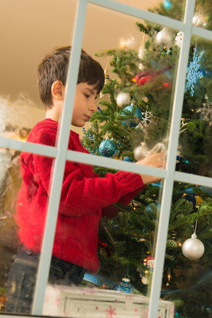 Boy decorating christmas tree in front of window