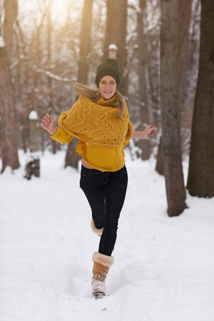 Woman running in snow in forest LANG_EVOIMAGES