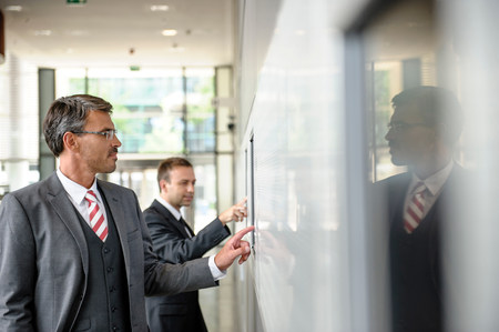 mirroring: Two businessmen interacting with touch screens