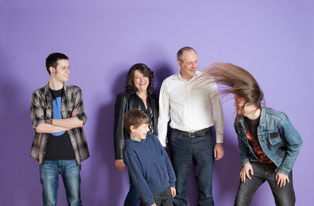 headbanging: Family watching son headbang in front of purple background