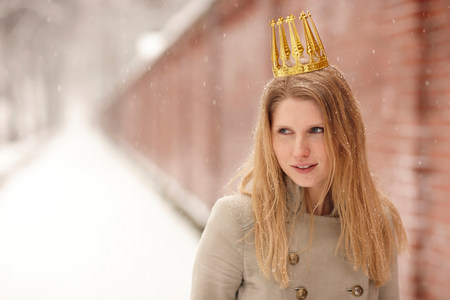 wintry weather: Woman wearing crown with brick wall behind her