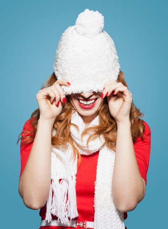 obscuring: Woman pulling white bobble hat over eyes