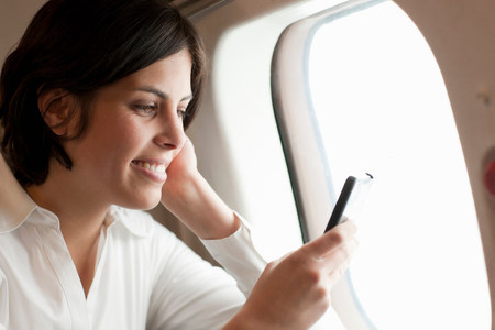 information superhighway: Candid portrait of young female looking at smartphone on aeroplane