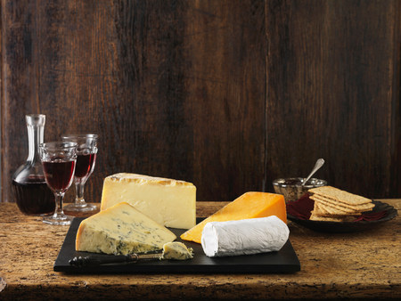 Speciality Christmas cheeseboard selection. Stilton,goats cheese,red leicester and cheddar with red wine and crackers LANG_EVOIMAGES