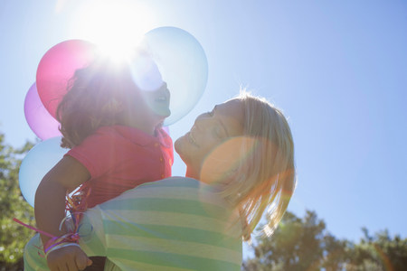 chillout: Mother hugging daughter in sunlight with basket of balloons