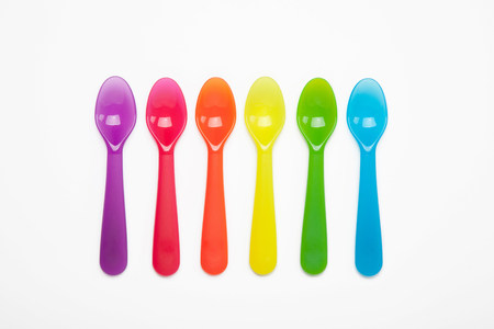 Colourful plastic spoons in a row