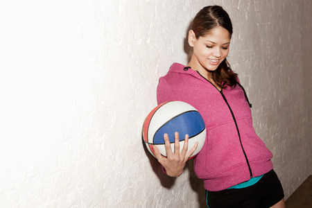 Young woman holding basketball LANG_EVOIMAGES