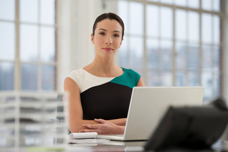 technology: Female office worker using laptop LANG_EVOIMAGES