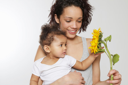 Baby girl touching sunflower held by mother in studio LANG_EVOIMAGES
