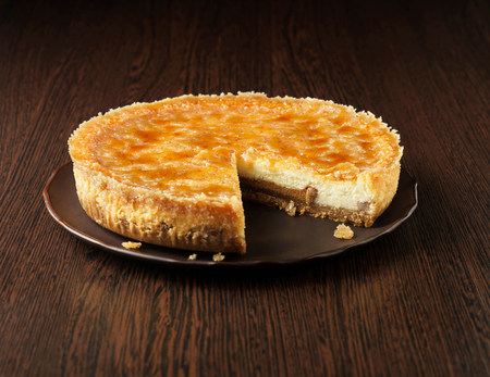 tempted: Toffee and pecan cheesecake on dark wooden plate and wooden surface LANG_EVOIMAGES