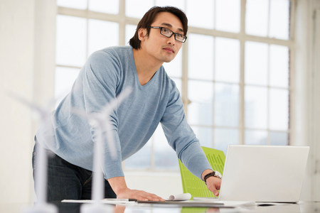 Man using laptop with models of wind turbines on desk LANG_EVOIMAGES